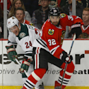 Chicago Blackhawks defenseman Michal Rozsival (32) tries to keep the puck away from Minnesota Wild left wing Matt Cooke (24) during the first period of an NHL hockey game in Chicago, Sunday, Jan. 11, 2015 The Associated Press