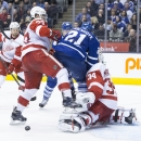 Toronto Maple Leafs' James van Riemsdyk (21) collides with Detroit Red Wings goaltender Petr Mrazek (34) while Detroit's Kyle Quincey (27) looks on during second period of an NHL hockey game in Toronto, Saturday, Dec. 13, 2014 The Associated Press