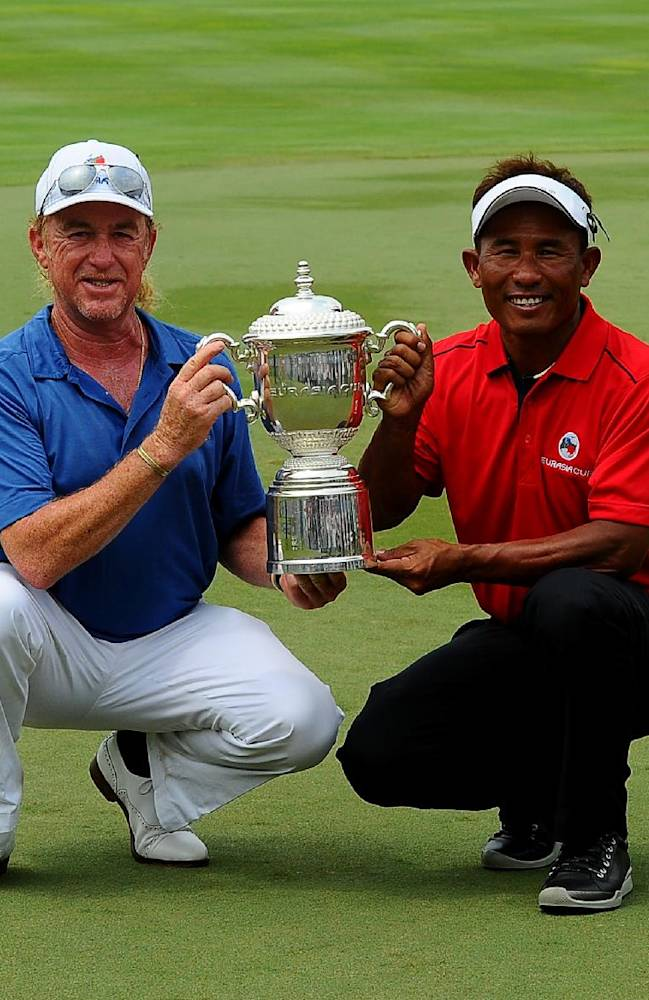 Miguel Angel Jimenez, left, of Spain and Thailand's Thongchai Jaidee, right, poses for the camera with the Eurasia trophy after both Team Asia and Euro drew during the third round of the Eurasia Cup golf tournament at the Glenmarie Golf and Country Club in Subang, Malaysia, Saturday, March 29, 2014