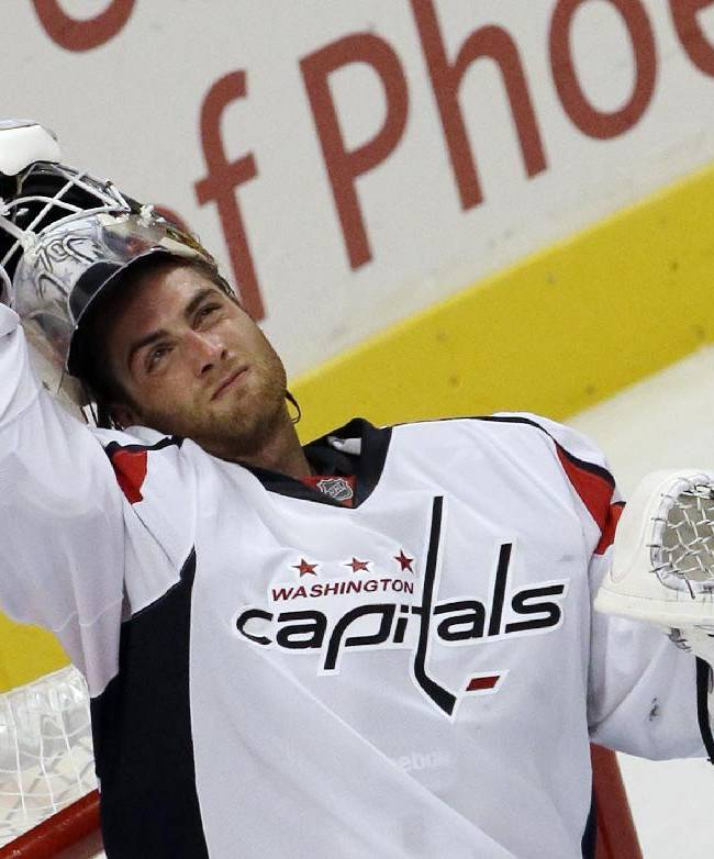 Washington Capitals goalie Braden Holtby (70) puts on his helmet during the third period of an NHL preseason hockey game against the Chicago Blackhawks in Chicago, Saturday, Sept. 28, 2013. The Blackhawks won 4-3