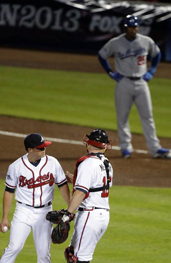 Atlanta Braves starting pitcher Kris Medlen, front left, speaks with catcher Brian McCann during the fourth inning of Game 1 of the National League Divisional Series against the Los Angeles Dodgers, Thursday, Oct. 3, 2013, in Atlanta