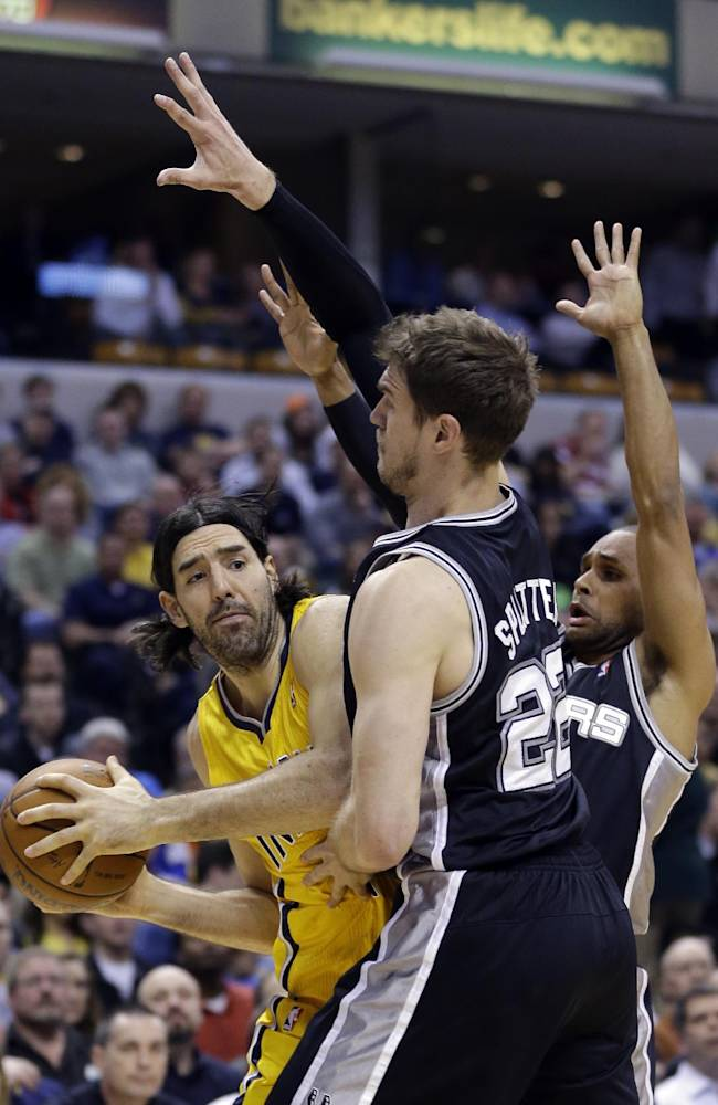 Indiana Pacers forward Luis Scola, left, is trapped by San Antonio Spurs center Tiago Splitter, center, and guard Patty Mills in the first half of an NBA basketball game in Indianapolis, Monday, March 31, 2014