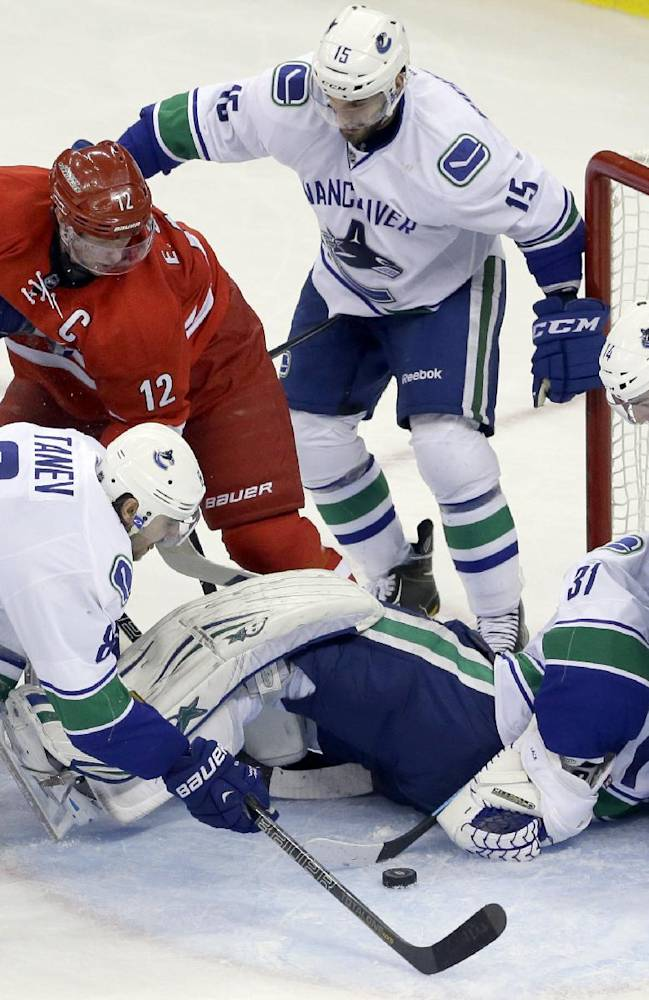 Carolina Hurricanes' Eric Staal (12) tries to score against Vancouver Canucks goalie Eddie Lack (31), of Sweden, as Canucks' Dan Hamhuis (2), Chris Tanev (8), Alex Burrows (14) and Brad Richardson (15) defend during the third period of an NHL hockey game in Raleigh, N.C., Sunday, Dec. 1, 2013. Vancouver won 3-2