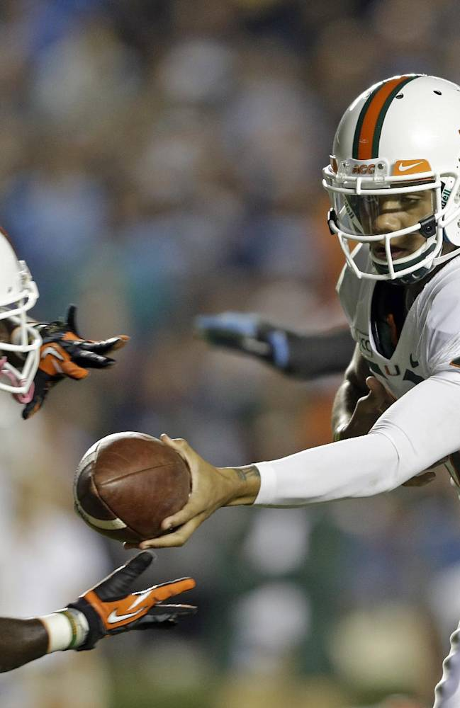 Miami quarterback Stephen Morris (17) hands off to Dallas Crawford (25) during the first half of an NCAA college football game against North Carolina in Chapel Hill, N.C., Thursday, Oct. 17, 2013