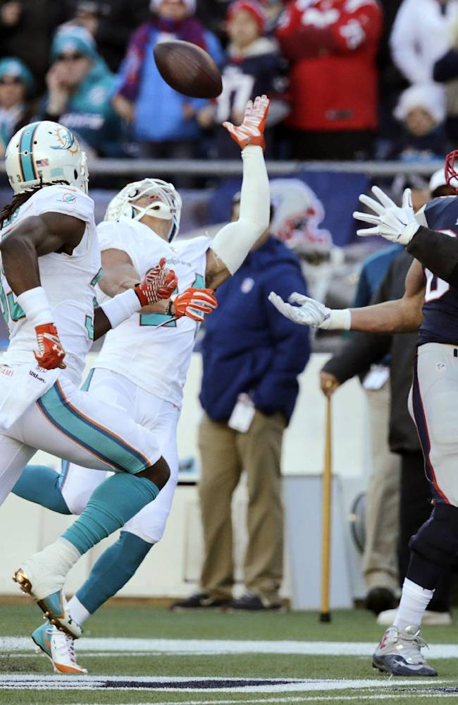 Miami Dolphins cornerback Cortland Finnegan, center, breaks up a pass intended for New England Patriots tight end Rob Gronkowski, right, in the first half of an NFL football game, Sunday, Dec. 14, 2014, in Foxborough, Mass