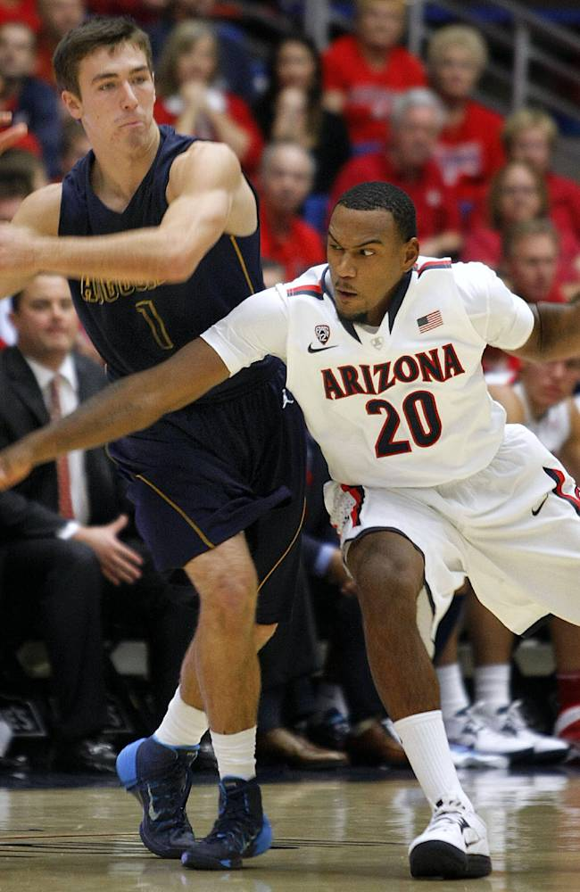 Arizona's Jordin Mayes (20) knocks the ball away from Augustana's Austin Saugstad (1) in the first half of an college exhibition basketball game, Monday, Oct. 28, 2013 in Tucson, Ariz