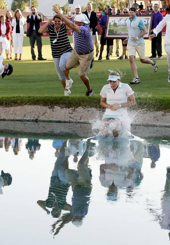 Lexi Thompson jumps into Poppy's Pond after winning the Kraft Nabisco Championship golf tournament Sunday, April 6, 2014, in Rancho Mirage, Calif