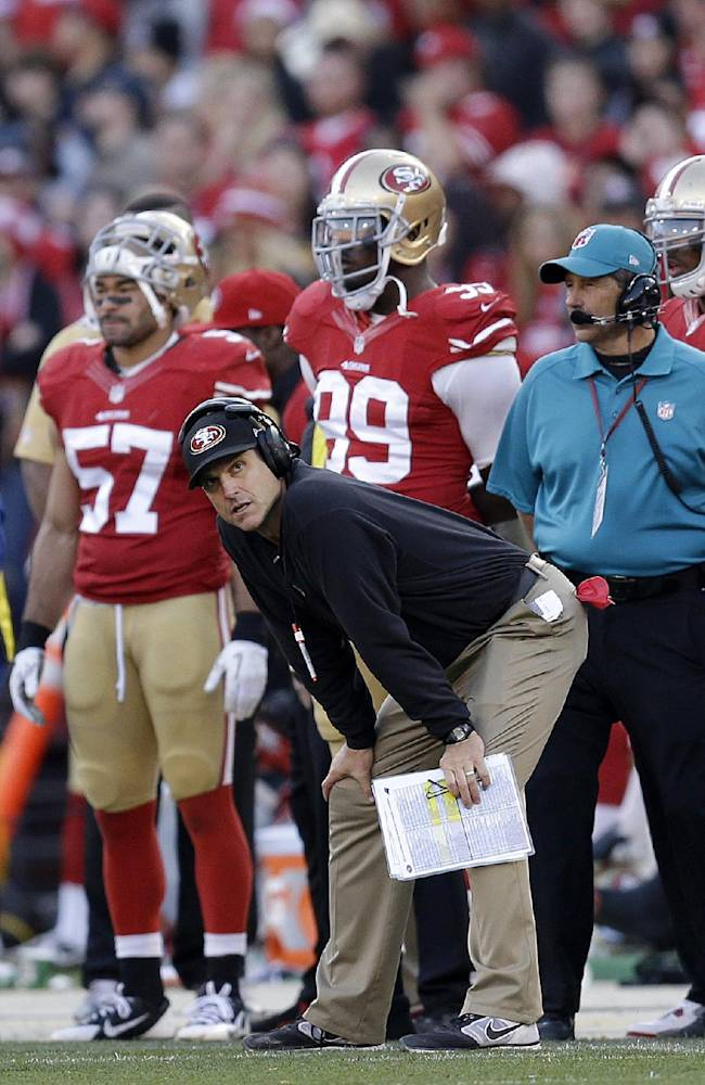 San Francisco 49ers head coach Jim Harbaugh watches from the sideline with linebacker Michael Wilhoite (57) and linebacker Aldon Smith (99) during the fourth quarter of an NFL football game against the Carolina Panthers in San Francisco, Sunday, Nov. 10, 2013