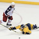 Nashville Predators center Filip Forsberg (9), of Sweden, falls to the ice attempting to pass the puck as he is defended by Columbus Blue Jackets defenseman James Wisniewski (21) in the second period of an NHL hockey game Saturday, Nov. 29, 2014, in Nashv