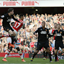 Arsenal's Alexis Sanchez, second left, heads the ball towards goal, under pressure from Hull City's Andrew Robertson during the English Premier League soccer match between Arsenal and Hull City at the Emirates stadium in London Saturday, Oct.18, 2014
