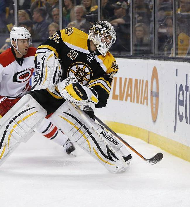 Boston Bruins' Chad Johnson (30) sends the puck along the boards in front of Carolina Hurricanes' Radek Dvorak (18) in the first period of an NHL hockey game in Boston, Saturday, March 15, 2014. The Bruins won 5-1