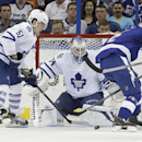 Toronto Maple Leafs goalie James Reimer (34) makes a save on a shot by Tampa Bay Lightning defenseman Eric Brewer (2) as Maple Leaf's defenseman Jake Gardiner (51) looks on during the first period of an NHL hockey game Tuesday, April 8, 2014, in Tampa, Fl