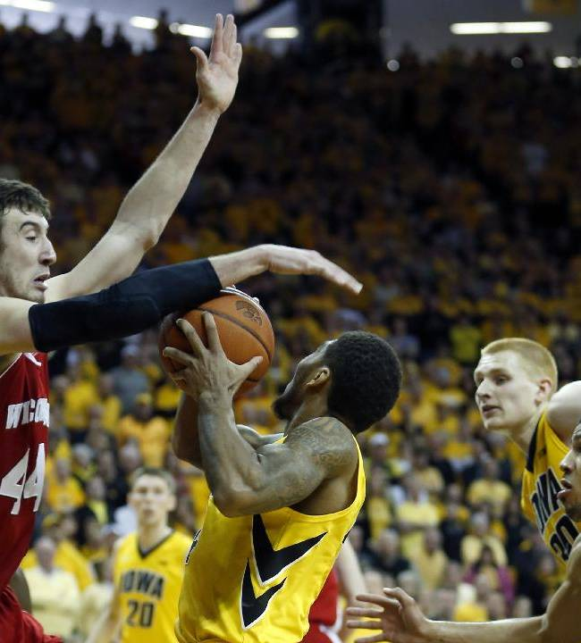 Wisconsin forward Frank Kaminsky stops the shot of Iowa guard Devyn Marble as he drives to the basket late in the second half of an NCAA college basketball game in Iowa City, Iowa, Saturday, Feb. 22, 2014. Wisconsin won 79-74