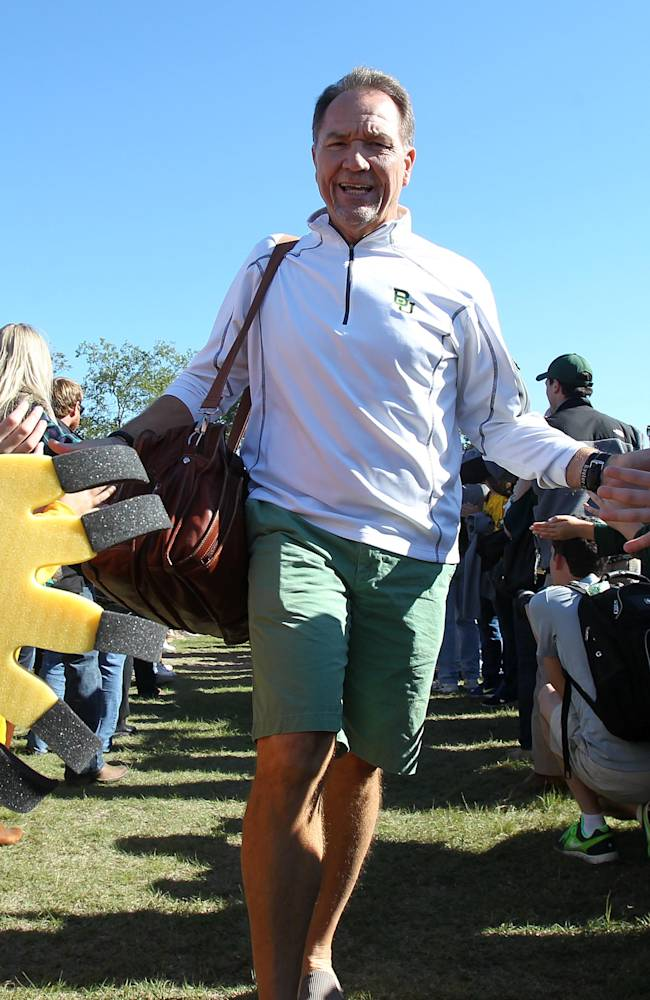 In this 2013 file photo Baylor defensive coach Phil Bennett is greeted by fans as he heads toward Floyd Casey Stadium football field in Waco, Texas. The Bears are allowing only 15 points and 306 total yards a game. That is best in the league and top 10 nationally for a group that gave up 37 points and nearly 500 yards a game while among the nation's 10-worst defenses the previous two seasons