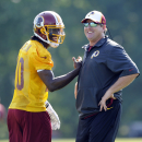 FILE - In this June 17, 2014, file photo, Washington Redskins quarterback Robert Griffin III, left, laughs with head coach Jay Gruden during NFL football minicamp in Ashburn, Va. It didn't take long for Gruden to figure out Robert Griffin III.