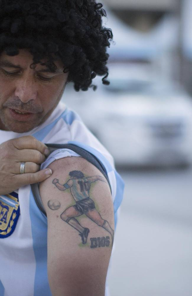 Street performing mime, Daniel Gonzalez, 35, who is dressed to resemble Argentine soccer great Maradona, shows his tattoo with the image of the argentine soccer player and the word God in Spanish underneath, in front of Maracana stadium, Rio de Janeiro, Brazil, Wednesday, June 11, 2014. The World Cup soccer tournament starts Thursday