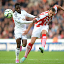 Stoke City's Erik Pieters, right, and Swansea City's Nathan Dyer battle for the ball during their English Premier League soccer match at the Britannia Stadium, Stoke, England, Sunday, Oct. 19, 2014