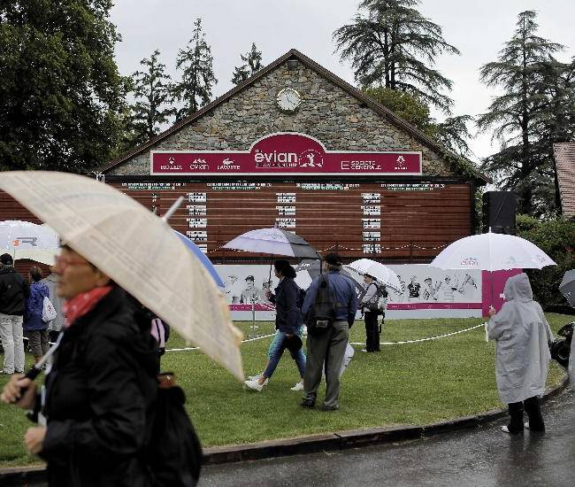 Supporters wait for the first round of the Evian Championship women's golf tournament in Evian, eastern France, to resume after a rain delay, Wednesday, Sept. 12, 2013