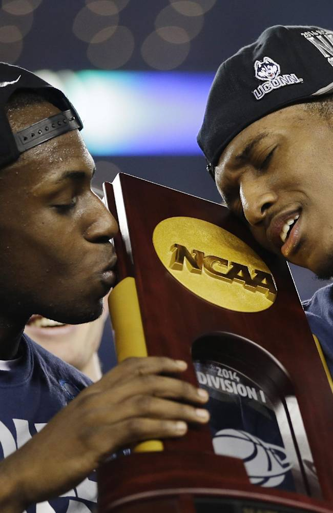 Connecticut guard Terrence Samuel, left, and guard Lasan Kromah hold the championship trophy after beating Kentucky 60-54, at the NCAA Final Four tournament college basketball championship game Monday, April 7, 2014, in Arlington, Texas