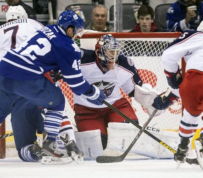 Toronto Maple Leafs Tyler Bozak, left, shoots on Columbus Blue Jackets goalie Segei Bobrovsky during the first period of an NHL hockey game in Toronto on Monday, March 3, 2014