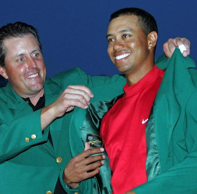 In tis April 10, 2005, file photo, Tiger Woods, right, gets the green jacket from Phil Mickelson, left, after winning the  Masters golf tournament at the Augusta National Golf Club in Augusta, Ga