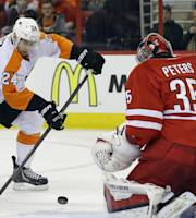 Carolina Hurricanes goalie Justin Peters (35) guards the net against Philadelphia Flyers' Matt Read (24) during the first period of an NHL hockey game in Raleigh, N.C., Tuesday, Nov. 5, 2013. (AP Photo/Gerry Broome)