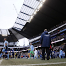 Manchester City's Vincent Kompany, left leads out his side on to the pitch as he holds the hand of a mascot prior to the start of the English Premier League soccer match between Manchester City and Arsenal at the Etihad Stadium, Manchester, England, Sunda
