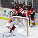 Carolina Hurricanes goalie Cam Ward, bottom, kneels at his goal while members of the New Jersey Devils celebrate a goal by Jaromir Jagr, of the Czech Republic, during the third period of an NHL hockey game, Wednesday, Nov. 27, 2013, in Newark, N.J. The Hu