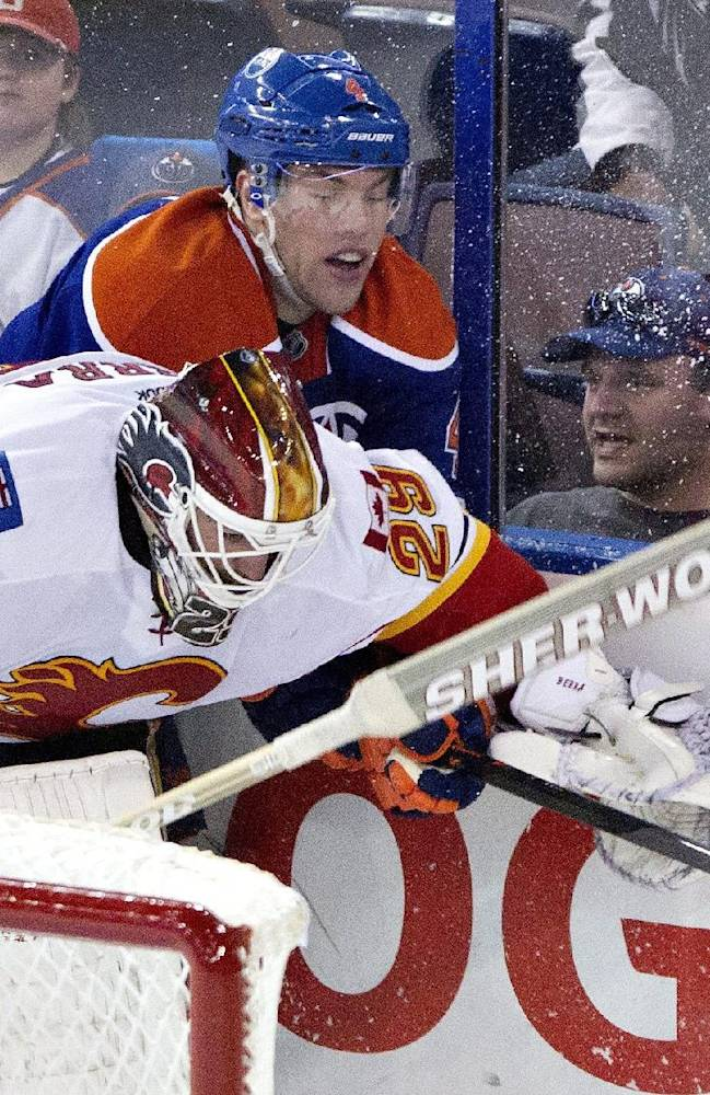 Calgary Flames goalie Reto Berra (29) is hit by Edmonton Oilers' Taylor Hall (4) during third period NHL hockey action in Edmonton, Alberta, on Saturday March 1, 2014