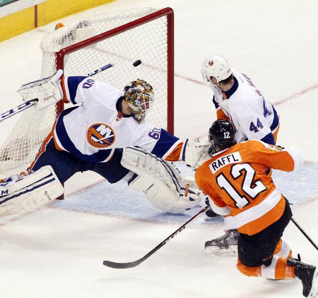 Philadelphia Flyers' Michael Raffl, right, scores the game-winning shot past New York Islanders goalie Kevin Poulin and as Calvin de Haan watches during the third period of an NHL hockey game, Saturday, Jan. 18,  2014, in Philadelphia. The Flyers won 6-4