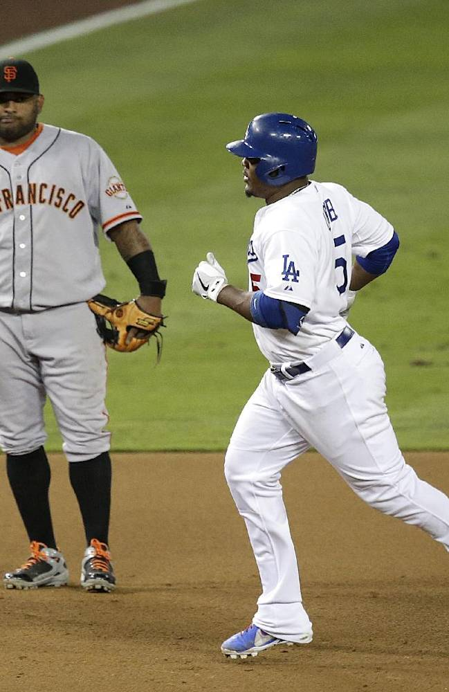 Los Angeles Dodgers' Juan Uribe, right, rounds the bases past San Francisco Giants' Pablo Sandoval after hitting a two-run home run during the sixth inning of a baseball game on Friday, Sept. 13, 2013, in Los Angeles