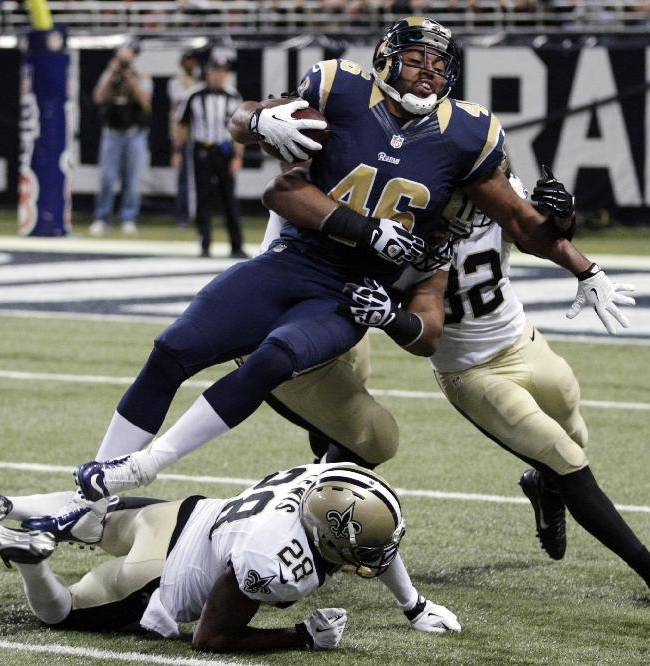 St. Louis Rams tight end Cory Harkey, center, struggles for yardage as New Orleans Saints cornerback Keenan Lewis (28) and safety Kenny Vaccaro, right, defend during the first quarter of an NFL football game Sunday, Dec. 15, 2013, in St. Louis