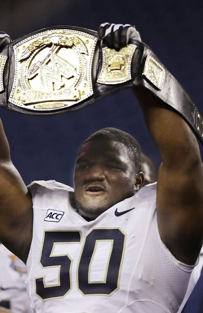 Pittsburgh defensive lineman Tyrone Ezell holds up a wrestling championship belt after the Panthers defeated Bowling Green 30-27 in the Little Caesars Pizza Bowl NCAA college football game, Thursday, Dec. 26, 2013, in Detroit