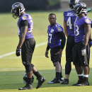 Baltimore Ravens running back Ray Rice, center, stretches before NFL football training camp practice, Thursday, July