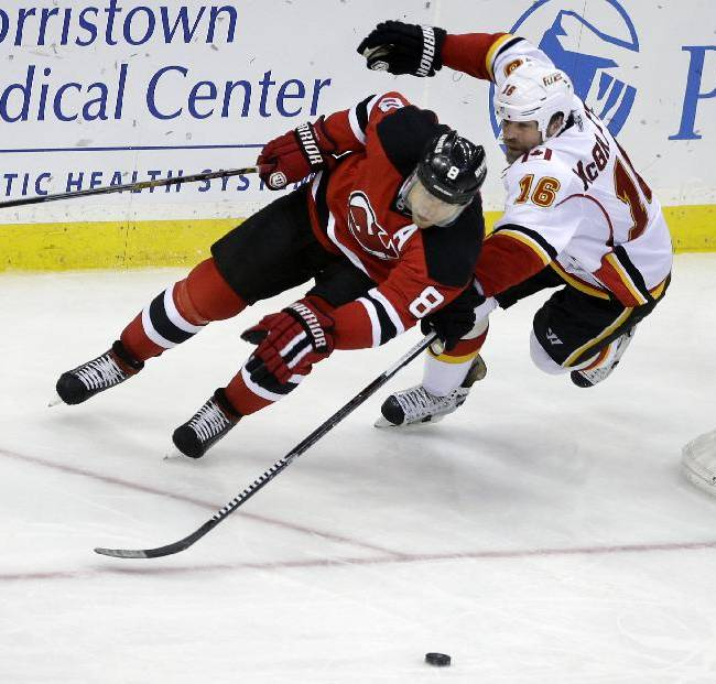New Jersey Devils' Dainius Zubrus (8), of Lithuania, chases the puck with Calgary Flames' Brian McGrattan (16) during the third period of an NHL hockey game in Newark, N.J., Monday, April 7, 2014. The Flames won 1-0