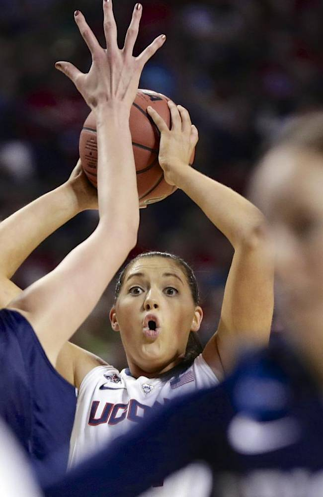 Connecticut's Stefanie Dolson, center, defended by BYU's Jennifer Hamson, second left, looks to pass during the first half of a regional semifinal in the NCAA college basketball tournament in Lincoln, Neb., Saturday, March 29, 2014
