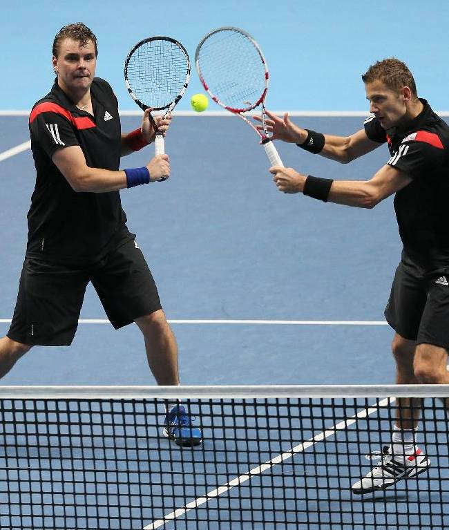 Mariusz Fyrstenberg of Poland, right, and Marcin Matkowski of Poland play a return to Bob Bryan of the United States and Mike Bryan of the United States during their ATP World Tour Finals tennis match at the O2 Arena in London, Saturday, Nov. 9, 2013