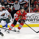 Chicago Blackhawks' Andrew Shaw (65) skates past Minnesota Wild's Matt Cooke (24) in the first period of an NHL hockey game in Chicago, Thursday, April 3, 2014 The Associated Press