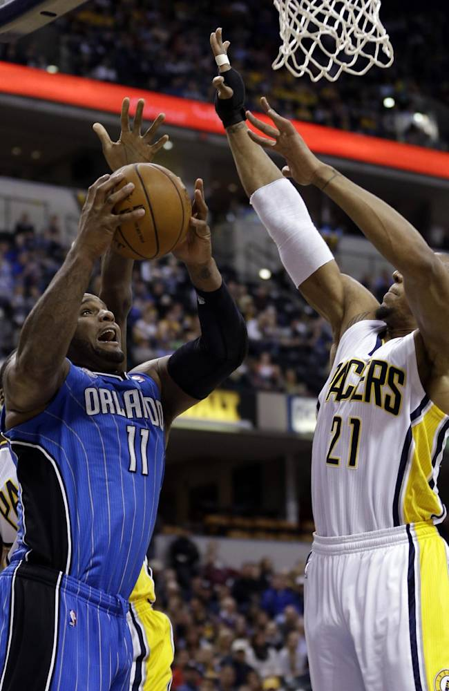 Orlando Magic forward Glen Davis, left, looks to shoot under Indiana Pacers forward David West in the first half of an NBA basketball game in Indianapolis, Monday, Feb. 3, 2014