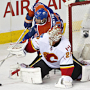 Calgary Flames goalie Reto Berra (29) makes the stop as Edmonton Oilers' Ryan Smyth (94) goes for the rebound during third period NHL hockey action in Edmonton, Alberta., on Saturday Dec. 7, 2013 The Associated Press
