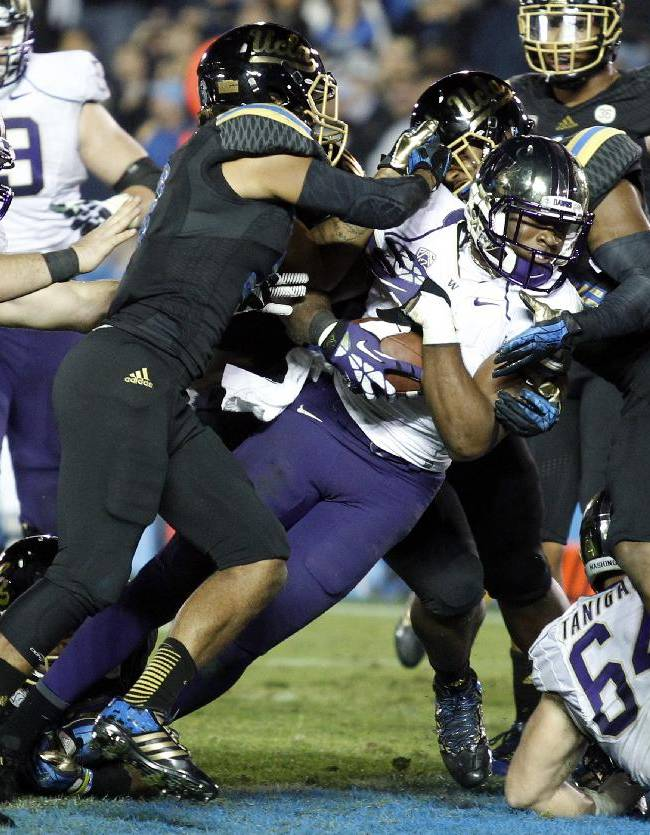 Washington wide receiver Damore'ea Stringfellow, center,  scores a 14-yard touchdown against UCLA in the fourth quarter of their NCAA college football game Friday, Nov. 15, 2013, in Pasadena, Calif. UCLA won the game 41-31