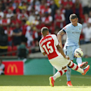 Arsenal's Alex Oxlade-Chamberlain, left, tackles Manchester City's Jesun Navas during the English FA Community Shield soccer match at Wembley Stadium, London Sunday, Aug. 10, 2014
