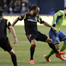 Los Angeles Galaxy's Landon Donovan, center, challenges Seattle Sounders midfielder Marco Pappa, right, in the second half of the second leg of the MLS western conference final soccer match, Sunday, Nov. 30, 2014, in Seattle. The match ended with a score