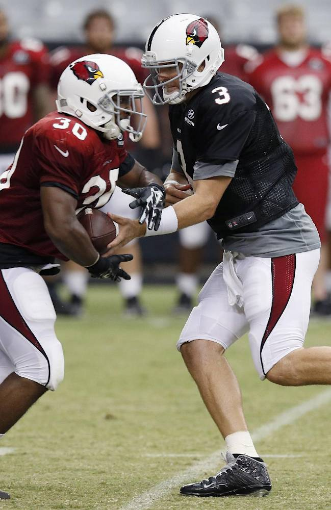 Arizona Cardinals' Carson Palmer (3) hands the ball off to Stepfan Taylor (30) during NFL football training camp practice on Wednesday, July 30, 2014, in Glendale, Ariz
