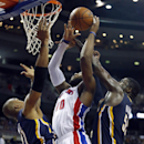 Detroit Pistons center Greg Monroe (10) goes to the basket between Indiana Pacers forward David West (21) and center Roy Hibbert (55) during the second half of an NBA basketball game Tuesday, Nov. 5, 2013, in Auburn Hills, Mich The Associated Press