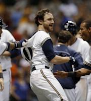 Milwaukee Brewers' Jonathan Lucroy is mobbed by teammates after hitting a walk-off, two-run home run during the ninth inning of a baseball game against the Cincinnati Reds on Friday, Aug. 16, 2013, in Milwaukee. The Brewers won 7-6. (AP Photo/Morry Gash)