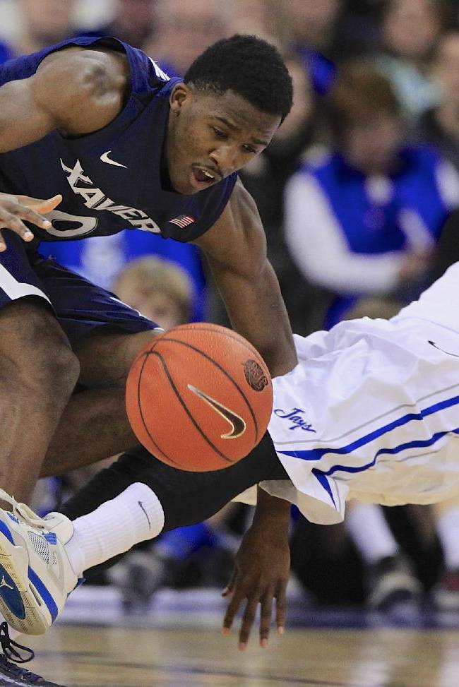 Xavier's Semaj Christon (0) fouls Creighton's Jahenns Manigat (12) in the first half of an NCAA college basketball game in Omaha, Neb., Sunday, Jan. 12, 2014