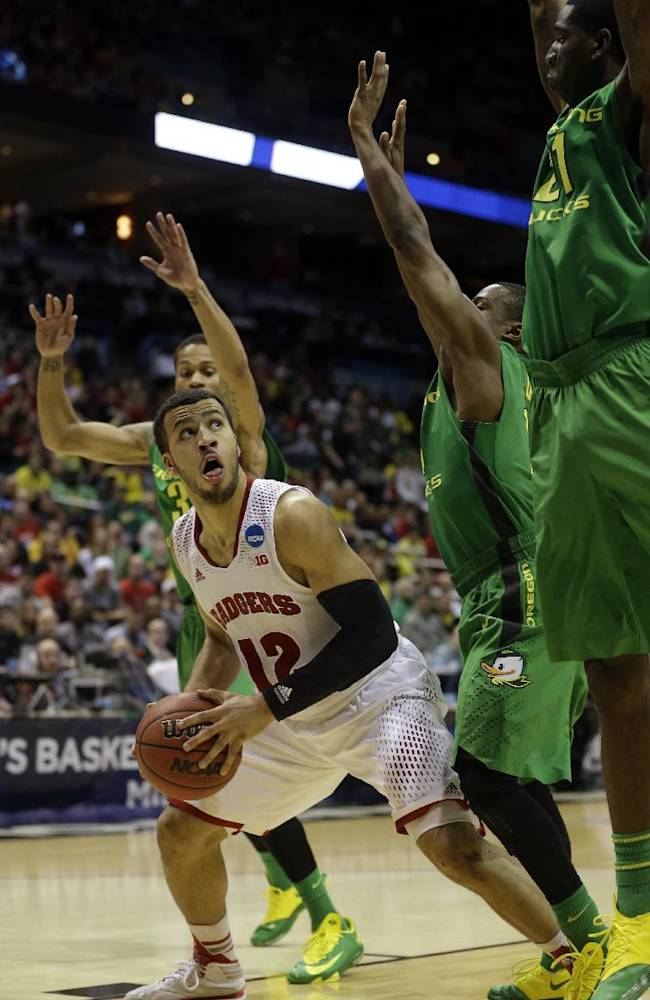 Wisconsin guard Traevon Jackson (12) drives to the basket against Oregon defense during the second half of a third-round game of the NCAA college basketball tournament Saturday, March 22, 2014, in Milwaukee