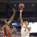 Georgia's John Florveus, left, tries to block a two-point shot by Florida guard Mike Rosario (3) during the first half of an NCAA college basketball game in Gainesville, Fla., Wednesday, Jan. 9, 2013. (AP Photo/Phil Sandlin)