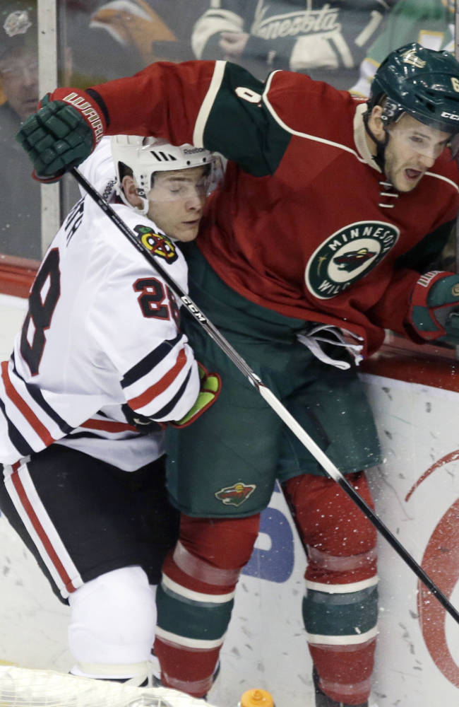 Chicago Blackhawks' Ben Smith, left, gets caught under the arm of Minnesota Wild's Marco Scandella in the first period of an NHL hockey game, Thursday, Jan. 23, 2014, in St. Paul, Minn